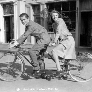 Glenn Ford and Rita Hayworth ride a bike.