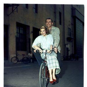 Grace Kelly and Jimmy Stewart ride a bike.