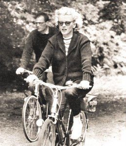 Marilyn Monroe and Arthur Miller ride bikes.