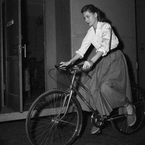 Lauren Bacall rides a bike.