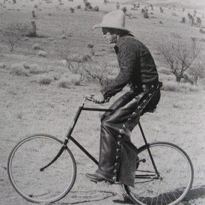 Steve McQueen rides a bike.