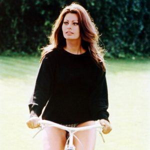 Sophia Loren rides a bike.