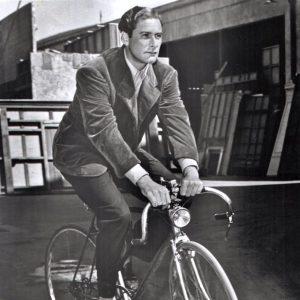 Errol Flynn rides a bike.