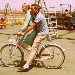 Paul Newman and Joanne Woodward ride a bike.