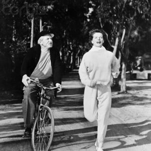 Spencer Tracy rides a bike. Katharine Hepburn runs.