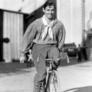 Clark Gable rides a bike.