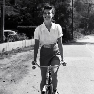 Ava Gardner rides a bike.