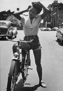 Eartha Kitt rides a bike.