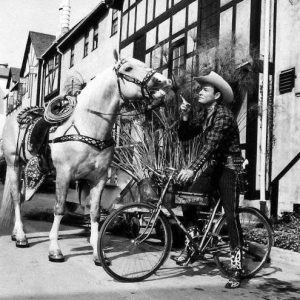 Roy Rogers rides a bike.