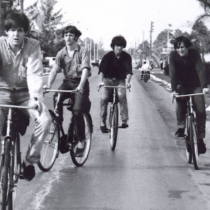 Paul McCartney, Ringo Starr, George Harrison and John Lennon ride bikes.