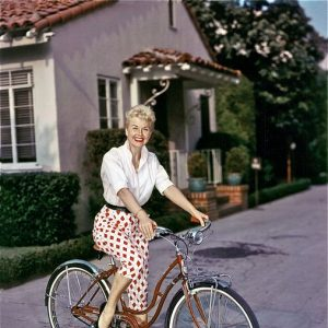 Doris Day rides a bike.