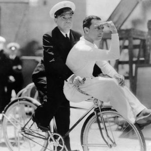 Cliff Edwards and Buster Keaton ride a bike.
