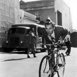 Bing Crosby rides a bike.