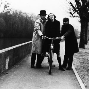 Anna Karina rides a bike. Sami Frey and Claude Brasseur help her out.