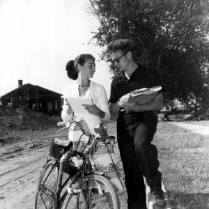 James Dean and Pier Angeli stand by a bike.
