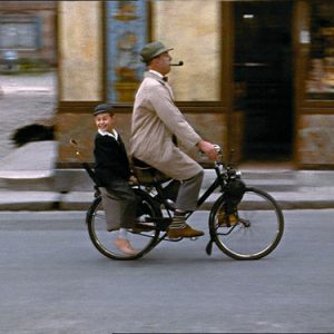 Jacques Tati and Alain Bécourt ride a bike.
