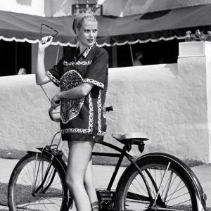 Grace Kelly stands by a bike.