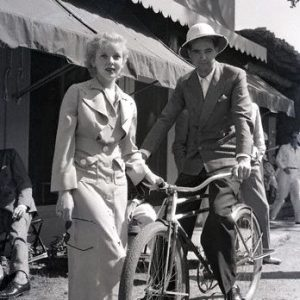 Howard Hughes rides a bike. Ida Lupino stands by.