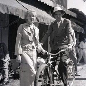 Howard Hughes rides a bike. Ida Lupino stands by.
