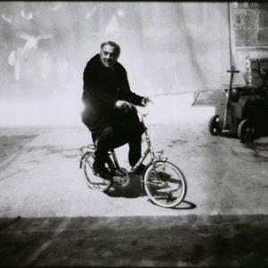 Federico Fellini rides a bike.