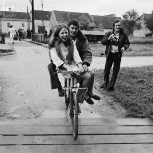 Alain Delon and Ottavia Piccolo ride a bike.