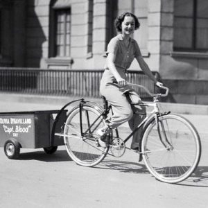 Olivia de Havilland rides a bike.