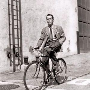 Humphrey Bogart rides a bike.