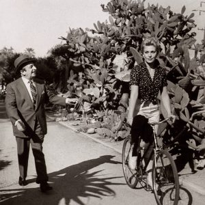 Kim Novak rides a bike. Louis Shurr points.