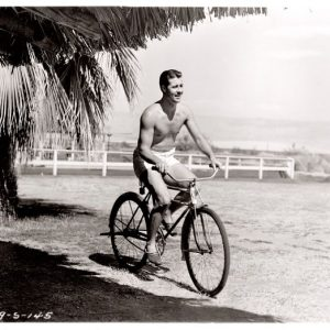 Don Ameche rides a bike. Shirtless.