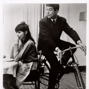 Jean-Claude Brialy rides a bike. Around Anna Karina's apartment.