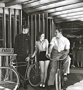 Buster Crabbe and Lona Andre park their bikes.
