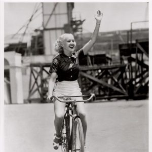 Betty Grable rides a bike.