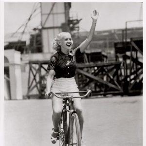 Betty Grable rides a bike.