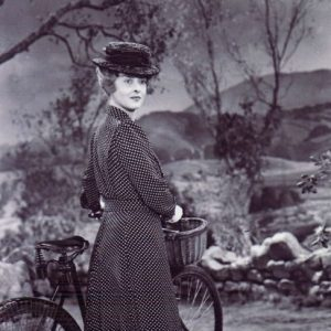 Bette Davis walks a bike.
