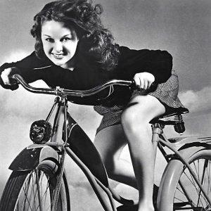 Susan Hayward rides a bike.
