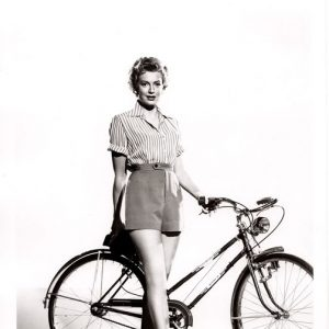 Deborah Kerr stands by a bike.