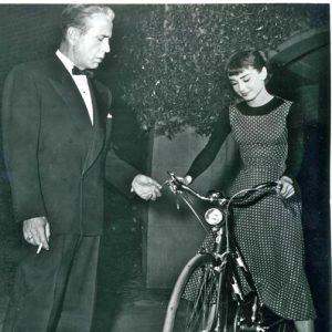 Audrey Hepburn rides a bike. Humphrey Bogart fiddles with the shifter.
