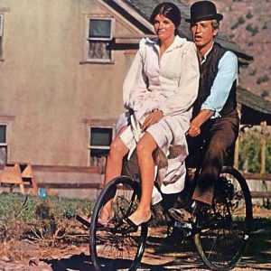 Paul Newman and Katharine Ross ride a bike.