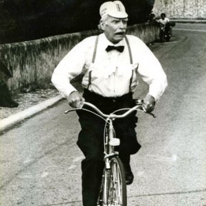 Laurence Olivier rides a bike.