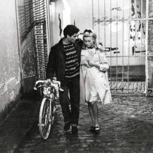 Nino Castelnuovo walks a bike. Catherine Deneuve walks alongside.