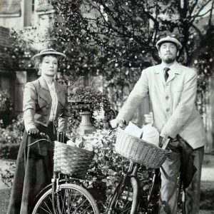Greer Garson and Walter Pidgeon stand by their bikes.
