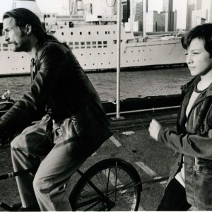 Jeff Bridges rides a bike. Edward Furlong runs alongside.
