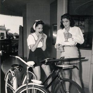 Dorothy Morris and Frances Rafferty ride bikes. For burgers.