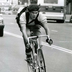 Kevin Bacon rides a bike.