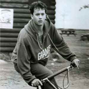 Tom Hanks rides a bike.