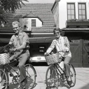 Jimmy Stewart and Gloria Hatrick McLean ride bikes. (And their dog rides, too.)