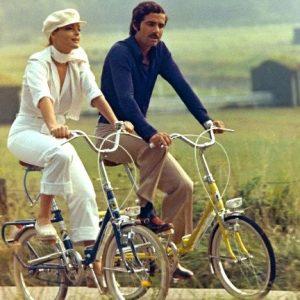 Romy Schneider and Nino Castelnuovo ride bikes.