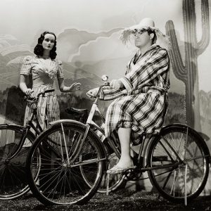 Bob Hope rides a bike. Wooden actress stands by hers.