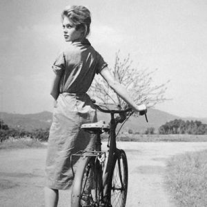 Brigitte Bardot walks a bike.