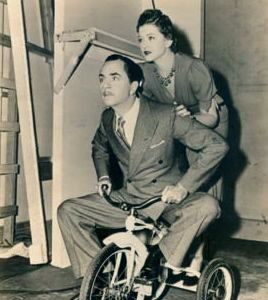William Powell and Myrna Loy ride a trike.